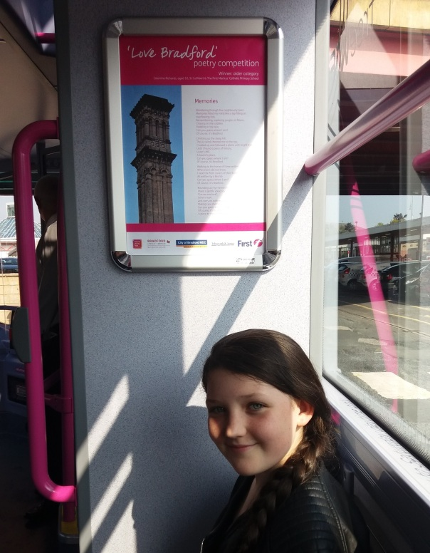 Winner of the Love Bradford poetry competition Caiomhe Richards, 11, with her winning entry which is framed inside a Bradford bus!